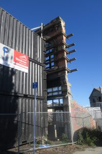 Building facade in downtown Christchurch propped up by stacked containers